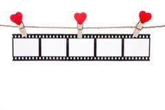 Clip en una guita, negativas colgantes, película de la forma del corazón del amor Imagen de archivo libre de regalías
