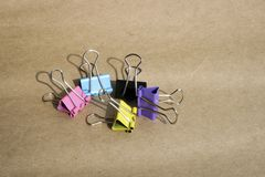Clip für Papier von verschiedenen Farben auf dem Hintergrund des rauen braunen Kraftpapiers briefpapier lizenzfreie stockfotos