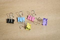 Clip f?r Papier von verschiedenen Farben auf dem Hintergrund des rauen braunen Kraftpapiers briefpapier lizenzfreie stockfotos