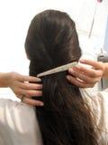 Clip on hair. A shine golden clip on long dark female hair Stock Images