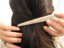 Clip on hair. A shine golden clip on long dark female hair Stock Image