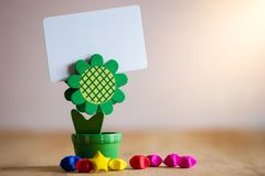 Clip holder card stand green sunflower shaped and multicolored paper stars. royalty free stock photos