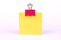 Clip rosado de la carpeta en el papel amarillo en blanco Imágenes de archivo libres de regalías