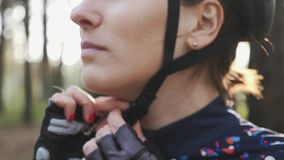 Clip sicure del ciclista in cablaggio del casco prima della corsa Fine in su Concetto di riciclaggio di sicurezza Movimento lento video d archivio