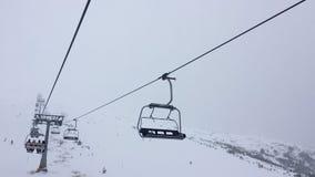 Clip vidéo de faute hyper de 1080 HD d'ascenseur de chaise pour quatre personnes de ski sur une montagne brumeuse clips vidéos