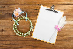 Clipboard attach planning paper with pen beside rose headband Royalty Free Stock Photo