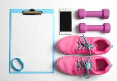 Clipboard with blank paper for exercise plan,. Gym stuff and mobile phone on white background. Flat lay composition Stock Images
