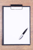 Clipboard with blank paper and pen on wooden table Royalty Free Stock Photos