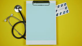 Clipboard with blank paper and pills in blisters. Concepts of drugs. Stop motion.  stock video