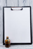 Clipboard with blank sheet of paper and bottle on wood background. Copy space.  Stock Image