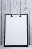 Clipboard with blank sheet of paper on wood background. Copy space.  Royalty Free Stock Images