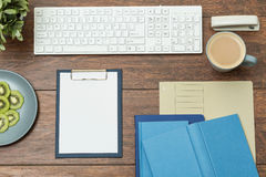 Clipboard and books. On wooden office desk royalty free stock image