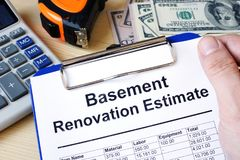 Clipboard with calculations basement renovation estimate. Remode. Clipboard with calculations basement renovation estimate and money. Remodel budget stock image
