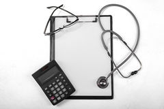 Clipboard with calculator and stethoscope Stock Images