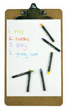 Clipboard with a childs to-do list and crayons Royalty Free Stock Photography