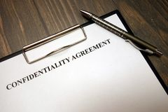 Clipboard with confidentiality agreement and pen on desk stock photo