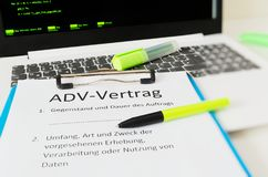 Clipboard with a contract and inscription in german ADV-Vertrag in english ADV contract and subject matter and duration of the con. Tract and scope type and stock photos