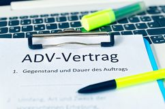 Clipboard with a contract and inscription in german ADV-Vertrag in english ADV contract and subject matter and duration of the con. Tract and scope type and royalty free stock image