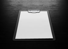 Clipboard with an empty sheet of paper on black wood background. Royalty Free Stock Photo