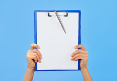 Clipboard in female hands on blue Royalty Free Stock Photography
