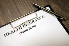 Clipboard with health insurance claim form and pen on desk. Clipboard with health insurance claim form and pen on wooden desk background stock photo