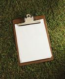 Clipboard Laying on grass. Clipboard with blank pages laying on grass Stock Photos