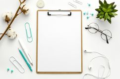 Clipboard mock up. Home office workspace flat lay mockup with clipboard, flowers and blue accessories. Flat lay, top. Home office workspace flat lay mockup with stock photography