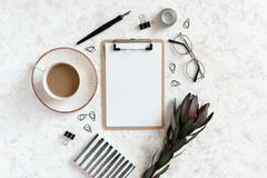 Clipboard mock up. Workspace with notepad, mug of coffee, stationery and accessories. On a beige textured background stock images