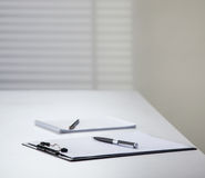 Clipboard and notebook with pens on a table Royalty Free Stock Images