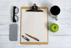 Clipboard with office supplies and snack foods on a white wooden Royalty Free Stock Photo