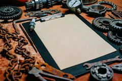 Clipboard with paper in the center of tools, gears on vintage metal background. Motorcycle equipment and repair. Top view. Clipboard with paper in the center of stock photo