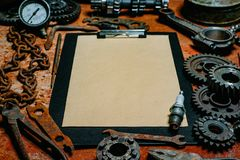 Clipboard with paper in the center of tools, gears on vintage metal background. Motorcycle equipment and repair. Clipboard with paper in the center of rusty royalty free stock image