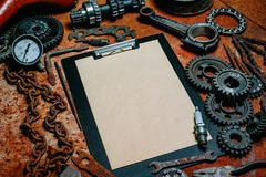 Clipboard with paper in the center of tools, gears on vintage metal background. Motorcycle equipment and repair. Top view. Clipboard with paper in the center of royalty free stock photos
