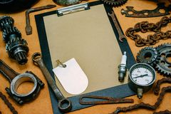 Clipboard with paper and oval label in the center of tools, gears on vintage fiberboard background. Motorcycle equipment and. Clipboard with paper and oval label royalty free stock photography