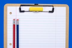 Clipboard Paper and Pencil. Clipboard with notebook paper, pencils and erasers arranged to provide copy space on paper Stock Photography