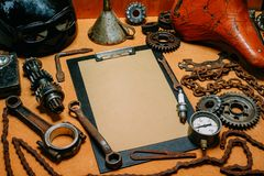 Clipboard with paper for your information in the center of tools, gears on vintage metal background. Motorcycle equipment and. Clipboard with paper for your royalty free stock image