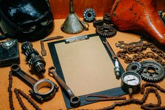 Clipboard with paper for your information in the center of tools, gears on vintage metal background. Motorcycle equipment and. Clipboard with paper for your royalty free stock images