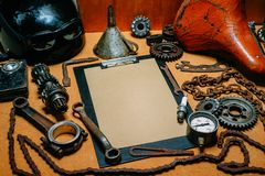 Clipboard with paper for your information in the center of tools, gears on vintage metal background. Motorcycle equipment and. Clipboard with paper for your stock images