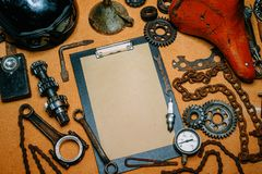 Clipboard with paper for your information in the center of tools, gears on vintage metal background. Top view. Clipboard with paper for your information in the royalty free stock image
