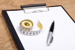 Clipboard, pen and measure tape on the table Stock Photography
