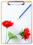 Clipboard with rose and pencil on white paper Stock Images