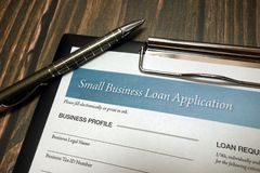 Clipboard with small business loan application form and pen on desk. Clipboard with small business loan application form and pen on wooden desk background stock images