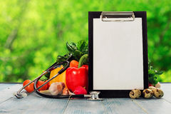 Clipboard with stethoscope and set of different vegetables. On wooden table. Healthy food concept Royalty Free Stock Photography
