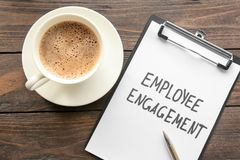 Clipboard with text EMPLOYEE ENGAGEMENT. And coffee on table Stock Image