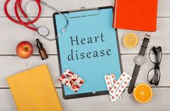 clipboard with text & x22;Heart disease& x22;, pills, stethoscope, eyeglasses royalty free stock photo