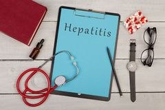 clipboard with text & x22;Hepatitis& x22;, pills, book, eyeglasses, watch and stethoscope royalty free stock photo