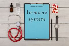Clipboard with text & x22;Immune system& x22;, pills, stethoscope and watch. Medecine concept - clipboard with text & x22;Immune system& x22;, pills, stethoscope Stock Images
