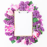 Clipboard, tulips and lilac branch on pink background. Flat lay, top view. Beauty blog concept. Clipboard, tulips and lilac branch on pink background. Flat lay Royalty Free Stock Image