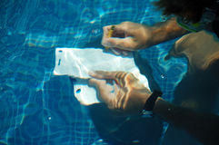 Clipboard Under Water. A clip board held under water with two hands by a diver.  One hand is holding a pencil Stock Image