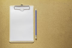 Clipboard with white paper and pencil on wooden table. Clipboard with white paper and pencil on wooden table top Stock Photo
